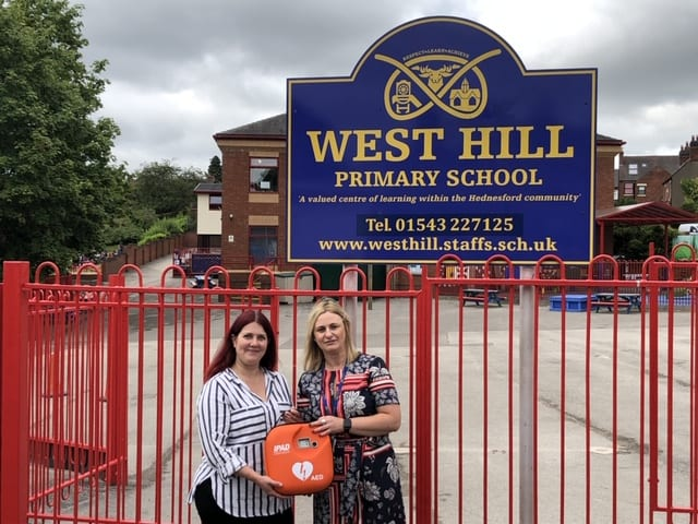 Helen Jackson from S2 Fire Solutions donating a defibrillator to West Hill Primary School, Cannock